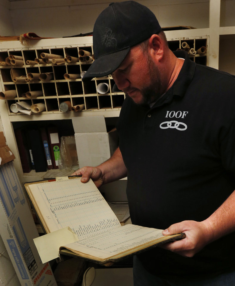 Photo -  IOOF Cemetery manager Tim Bowling looks through records in search of evidence of a mass grave of victims of a 1918 fire at the state mental hospital. PHOTO BY STEVE SISNEY, THE OKLAHOMAN   STEVE SISNEY -