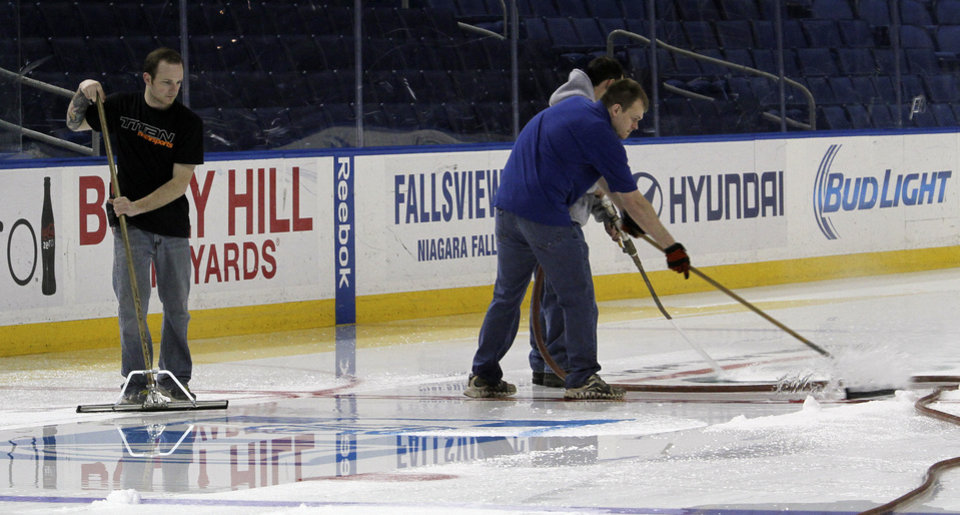 Photo - First Niagara Center arena workers remove the ice surface after players gathered for the last time on Monday, April 14, 2014, after the NHL hockey team clinched the NHL's worst record in Buffalo, N.Y. (AP Photo/Nick LoVerde)