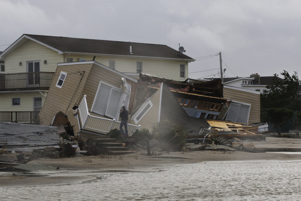 Photo -   A man photographs a home damaged during a storm at Breezy Point in the New York City borough of Queens Tuesday, Oct. 30, 2012. The fire destroyed between 80 and 100 houses Monday night in an area flooded by the superstorm that began sweeping through earlier. (AP Photo/Frank Franklin II)