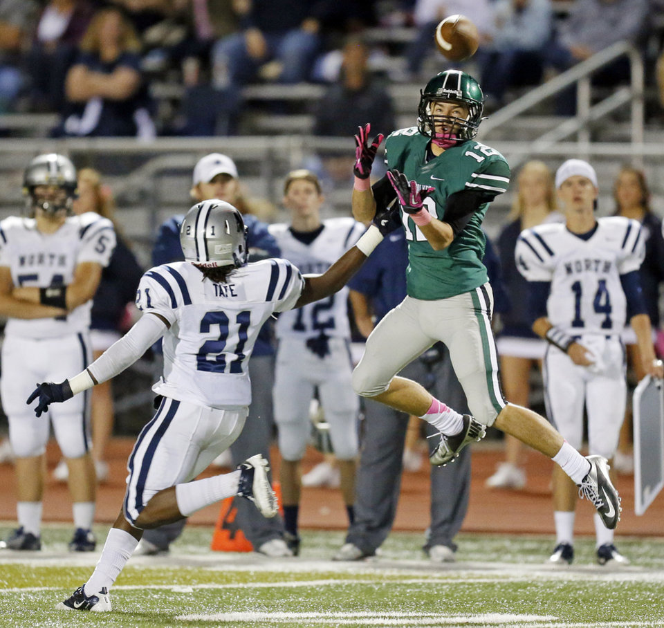 Photo - Norman North's Jake Higginbotham (12) makes a catch against Edmond North's Lindell Tate (21) during a high school football game between Edmond North and Norman North in Norman, Okla., Thursday, Oct. 11, 2012. Photo by Nate Billings, The Oklahoman