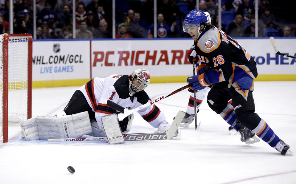 New Jersey Devils goalie Johan Hedberg, left, watches as New York Islanders' Matt Moulson tries to recover the puck during the second period of the NHL hockey game on Sunday, Feb. 3, 2013, in Uniondale, N.Y. (AP Photo/Seth Wenig)