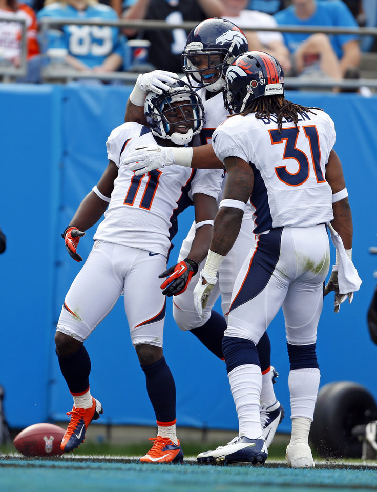 Denver Broncos\' Trindon Holliday (11) celebrates with teammates, including Omar Bolden (31), after returning a Carolina Panthers punt for a touchdown during the first half of an NFL football game in Charlotte, N.C., Sunday, Nov. 11, 2012. (AP Photo/Bob Leverone)