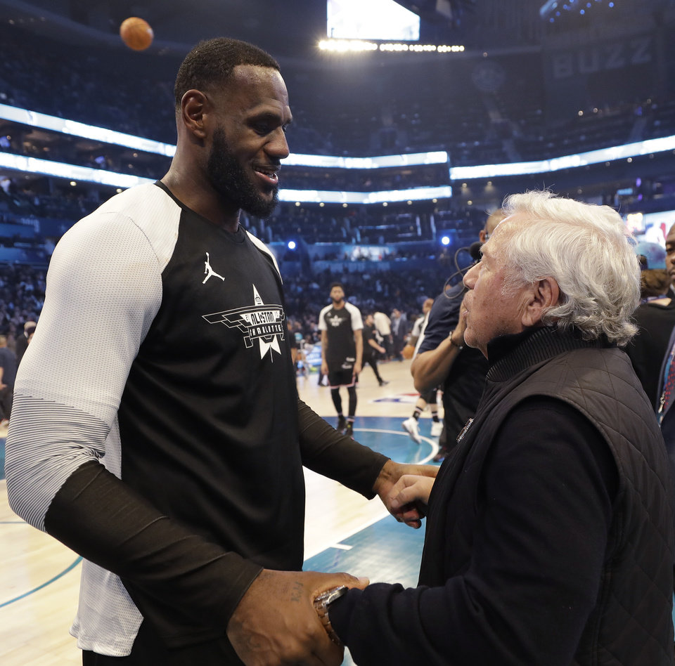 Photo - Team LeBron's LeBron James, of the Cleveland Cavaliers, left, speaks with New England Patriots Owner Robert Kraft during the second half of an NBA All-Star basketball game, Sunday, Feb. 17, 2019, in Charlotte, N.C. (AP Photo/Chuck Burton)