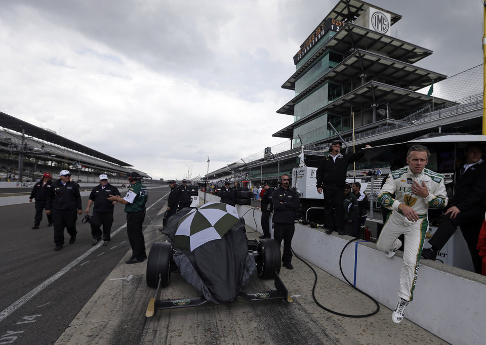 Photo - Driver Ed Carpente, right, jumps off the pit wall as rain halted activity on the first day of qualifications for Indianapolis 500 IndyCar auto race at the Indianapolis Motor Speedway in Indianapolis, Saturday, May 17, 2014. (AP Photo/Darron Cummings)