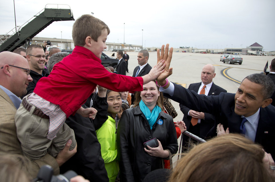 FILE - This Oct. 17, 2012 file photo shows President Barack Obama giving a high-five to a boy name Ryan as he greets people on the tarmac upon his arrival at Eastern Iowa Airport in Cedar Rapids, Iowa for a campaign stop. The president sports a pink bracelet in honor of October being breast cancer awareness month. Kiss by kiss, handshake by handshake, President Barack Obama glides across the perimeter of a small tennis stadium, stooping over to embrace white-haired retirees wearing dark sunglasses and extending his arms to shake hands or touch the masses a few rows back. (AP Photo/Carolyn Kaster, File)