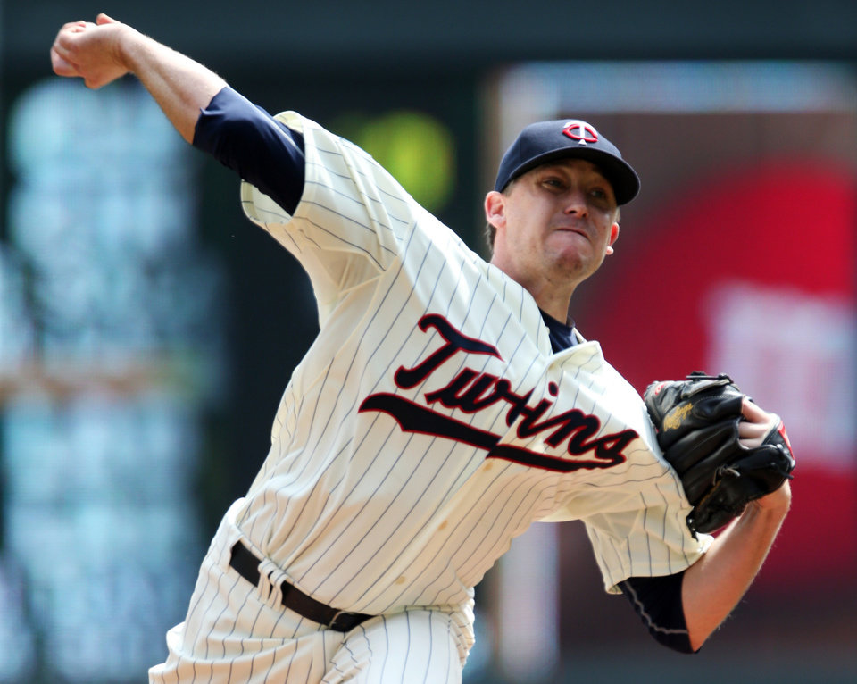 Photo - Minnesota Twins starting pitcher Kevin Correia throws against the San Diego Padres in the first inning of a baseball game, Wednesday, Aug. 6, 2014, in Minneapolis. (AP Photo/Jim Mone)