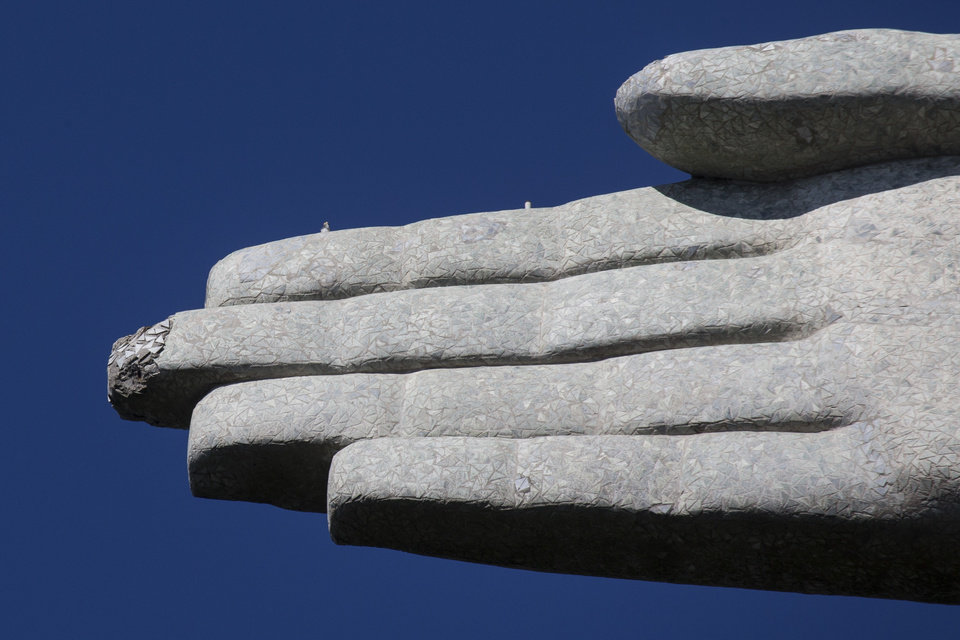 Photo - One of the fingers of the Christ Redeemer statue is chipped in Rio de Janeiro, Brazil, Tuesday, Jan. 21, 2014. The famed statue is being examined for repairs after two fingers and its head were chipped during recent lightning storms. Officials say they'll place more lightning rods on the statue in an effort to prevent future damage. (AP Photo/Felipe Dana)