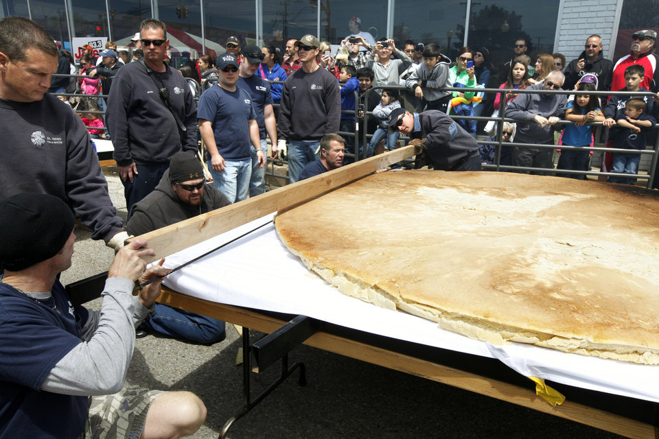 El Reno Fire Fighters slice a bun to hold a 750 lb. burger during the Fabulous Burger Day Festival in El Reno, OK, Saturday, May 4, 2013,  By Paul Hellstern, The Oklahoman
