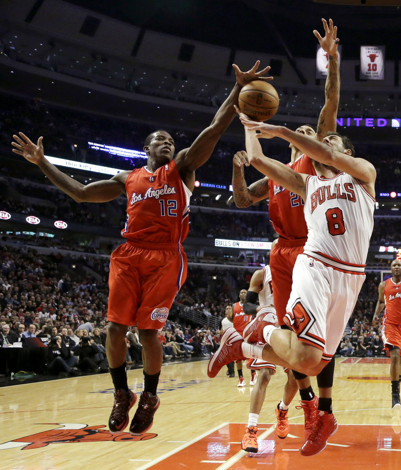 Photo - Los Angeles Clippers guard Eric Bledsoe (12) blocks a shot by Chicago Bulls guard Marco Belinelli (8) as Clippers' Matt Barnes also defends during the first half of an NBA basketball game, Tuesday, Dec. 11, 2012, in Chicago. (AP Photo/Charles Rex Arbogast)