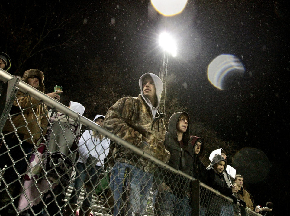 Photo - Blanchard fans bundle up in freezing rain to watch the Lions as Newcastle plays Blanchard in Class 3A high school football playoffs on Friday, Nov. 22, 2013, in Blanchard, Okla. Photo by Steve Sisney, The Oklahoman