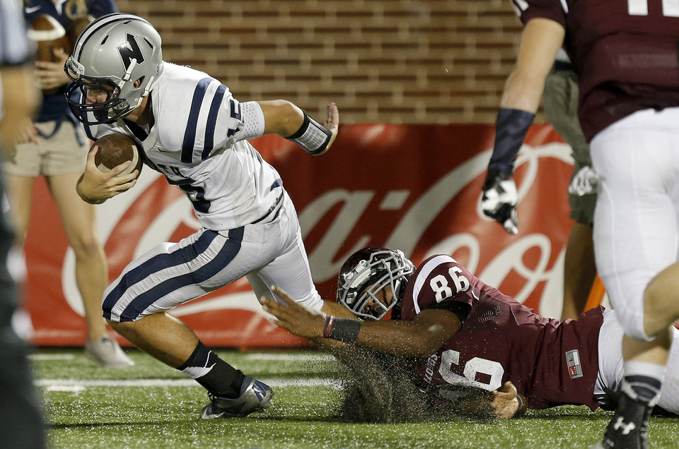 Photo - Edmond Memorial's Trayvon Gamble brings down Edmond North's Stephen McClernon Waylan Anderson during their high school football game at Wantland Stadium in Edmond, Friday, September 6, 2013. Photo by Bryan Terry, The Oklahoman