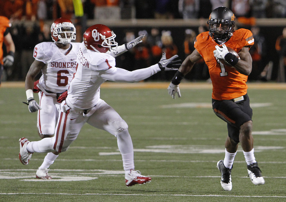 Photo - Joseph Randle (1) out runs Oklahoma's Tony Jefferson (1) during the Bedlam college football game between the Oklahoma State University Cowboys (OSU) and the University of Oklahoma Sooners (OU) at Boone Pickens Stadium in Stillwater, Okla., Saturday, Dec. 3, 2011. Photo by Chris Landsberger, The Oklahoman
