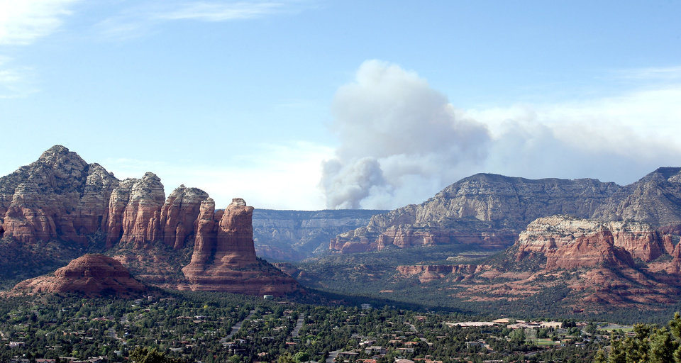 Photo - Smoke rises from the Slide Fire as it burns up Oak Creek Canyon on Thursday, May 22, 2014, in Sedona, Ariz.  The fire has burned approximately 4,800 acres. (AP Photo/Ross D. Franklin)