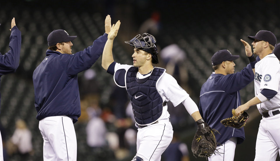 Photo - Seattle Mariners catcher Mike Zunino, center, shares congratulations with teammates after beating the Seattle Mariners in a baseball game Wednesday, Sept. 25, 2013, in Seattle. The Mariners won 6-0. (AP Photo/Elaine Thompson)