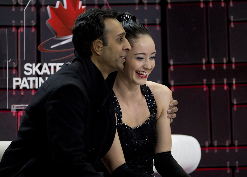 Photo - Coach Ravi Walia hugs Kaetlyn Osmond as her scores are posted following her short program at the Canadian figure skating championships Friday Jan. 10, 2014 in Ottawa. (AP Photo/The Canadian Press, Adrian Wyld)