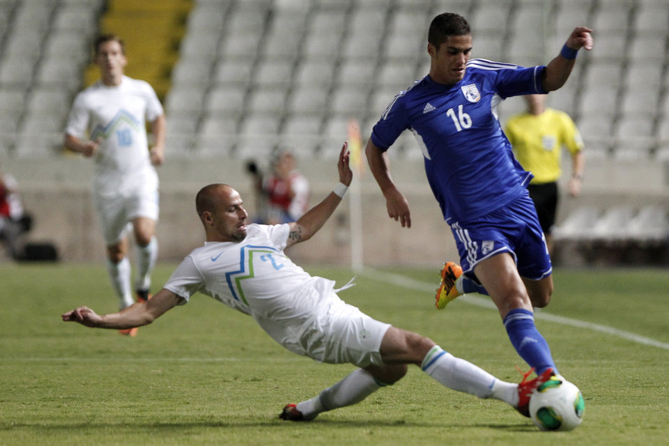 Photo - Cyprus' Petros Sotiriou, right, fights for the ball with Slovenia's Miso Brecko during their World Cup group E qualifying soccer match at GSP stadium in Nicosia, Cyprus, Tuesday, Sept. 10, 2013. (AP Photo/Petros Karadjias)