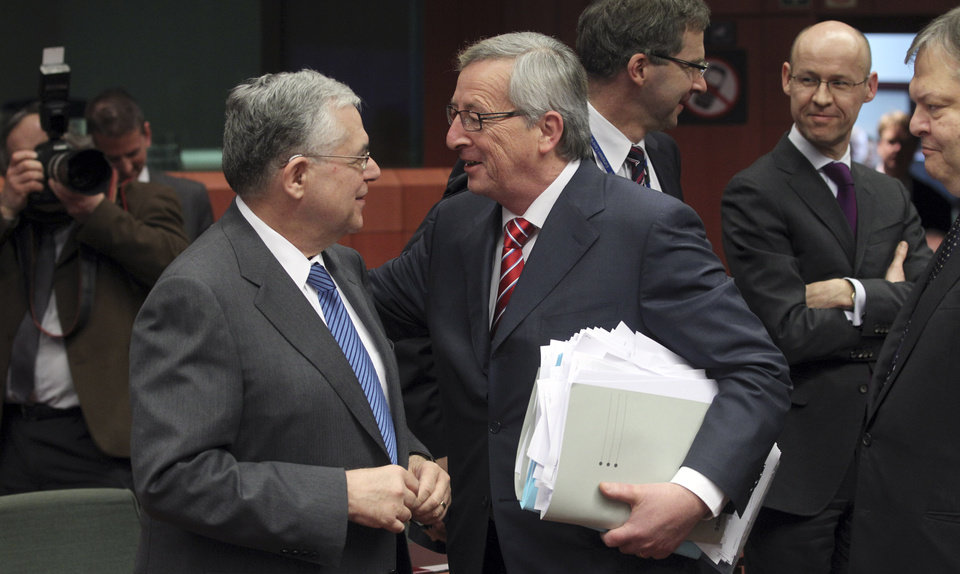 Photo -   Luxembourg's Prime Minister Jean-Claude Juncker, right, speaks with Greek Prime Minister Lucas Papademos, left, during a round table meeting of eurozone finance ministers at the EU Council building in Brussels on Monday, Feb. 20, 2012. Eurozone governments will likely approve on Monday a long-elusive rescue package for Greece, saving it from a potentially calamitous bankruptcy next month, senior officials said. But finance ministers meeting in Brussels will have a few last issues to wrangle over, such as tighter controls over Greece's spending and further cuts to the country's debt load. (AP Photo/Yves Logghe)