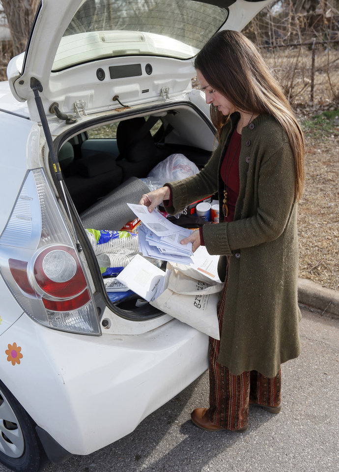 Photo - Jamie Zumwalt, 51, founder and pastor of Joe's Addiction, goes through mail to hand out to people eating lunch out of a tent at 6100 S Cox, near the original location of Joe's Addiction, in Valley Brook, Okla., Monday, Dec. 23, 2019. While the new site for Joe's Addiction is not ready, Zumwalt and others continue to help the community of people in need who were being served by Joe's Addiction. [Nate Billings/The Oklahoman]