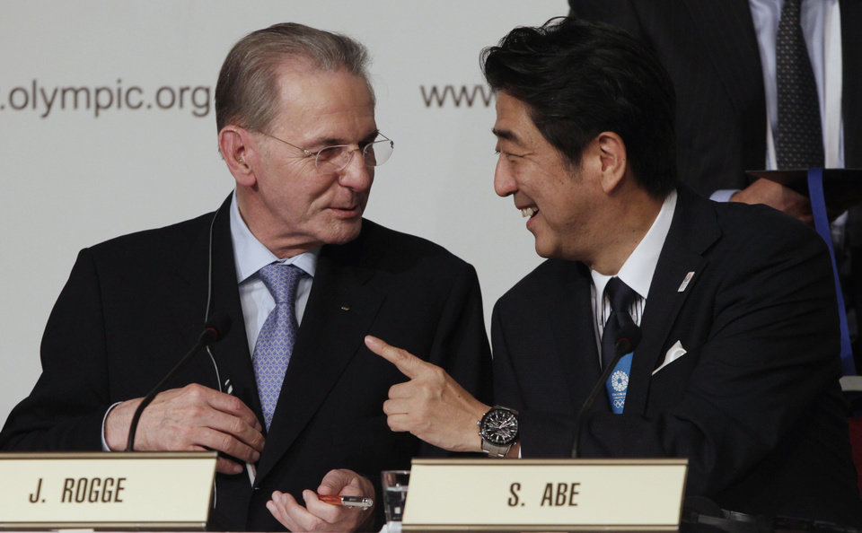 Photo - Japan's Prime Minister Shinzo Abe, right, and President of the International Olympic Committee Jacques Rogge talk after signing the Host City Contract after Tokyo was awarded the 2020 Olympic Games in Buenos Aires, Argentina, Saturday, Sept. 7, 2013. Tokyo defeated Istanbul in the final round of secret voting Saturday by the International Olympic Committee. Madrid was eliminated earlier after an initial tie with Istanbul. (AP Photo/Victor Caivano)