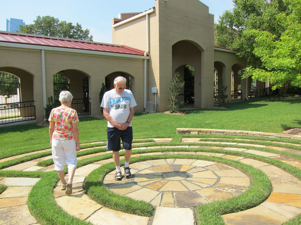 Photo - Kathy and Malcolm May, of Bethany, walk on a four-circuit labyrinth in the east garden of St. Paul's Episcopal Cathedral during