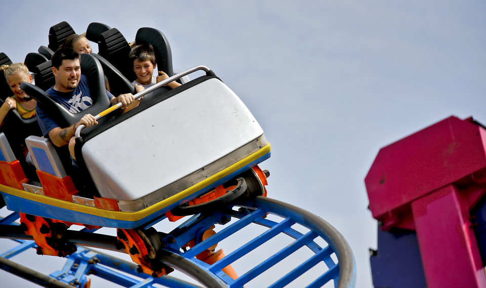 Photo - Visitors to the midway take a ride on the rollercoaster during the 2013 Oklahoma State Fair on Monday, Sep. 16, 2013. Photo by Chris Landsberger, The Oklahoman