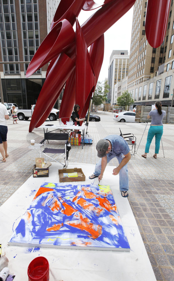 Photo - Artist Ty Kelly, Edmond, works on an acrylic painting at Leadership Square the OK Chefs Relief pop-up on Monday.  PAUL B. SOUTHERLAND - PAUL B. SOUTHERLAND