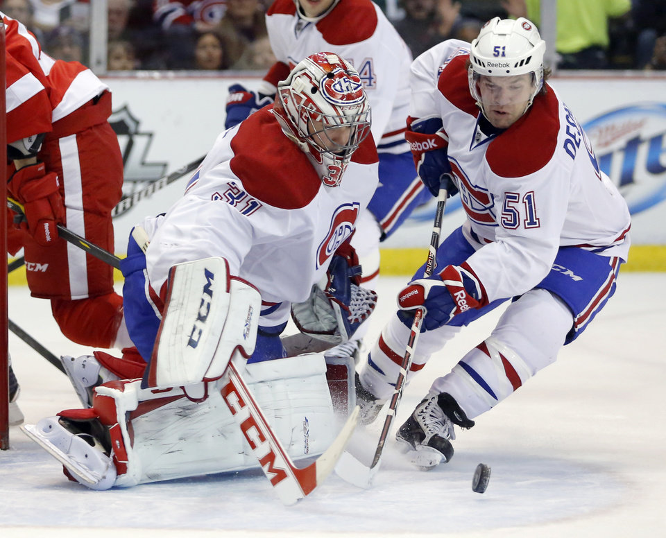 Photo - Montreal Canadiens goalie Carey Price (31) receives help stopping a shot from teammate David Desharnais (51) during the first period of an NHL hockey game against the Detroit Red Wings Thursday, March 27, 2014, in Detroit. (AP Photo/Duane Burleson)