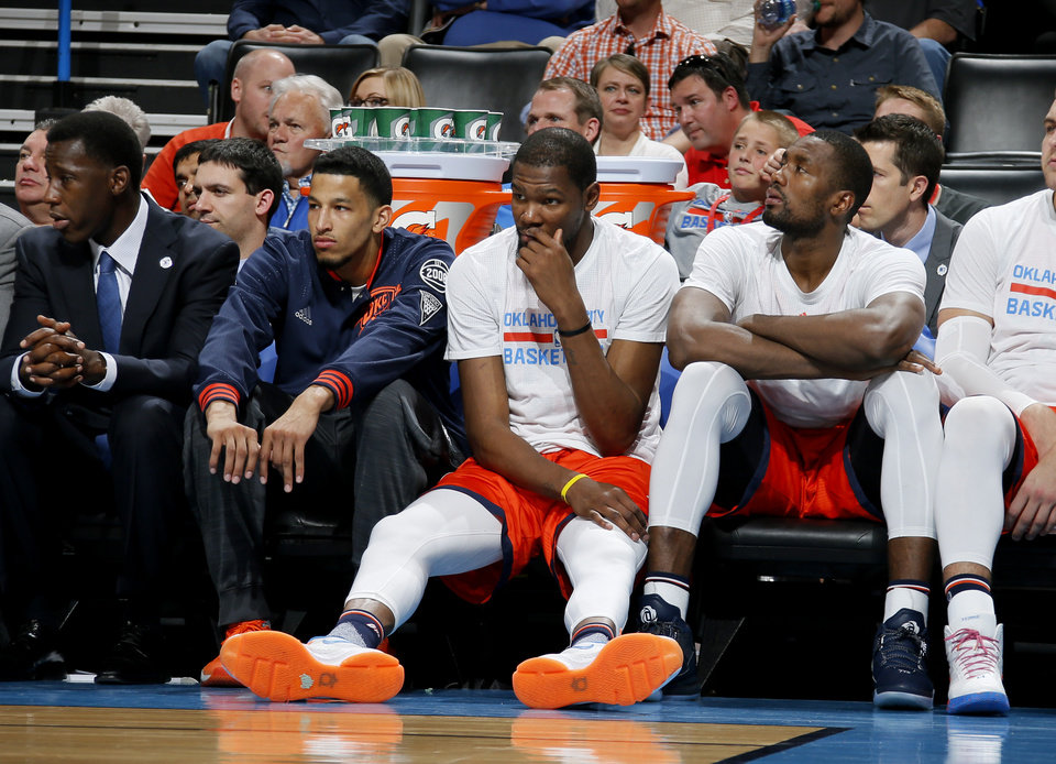 Photo - Oklahoma City's Andre Roberson, Kevin Durant and Serge Ibaka watch during the second half of an NBA basketball game between the Oklahoma City Thunder and the Cleveland Cavaliers at Chesapeake Energy Arena in Oklahoma City, Sunday, Feb. 21, 2016. Oklahoma City lost 115-92.  Photo by Bryan Terry, The Oklahoman