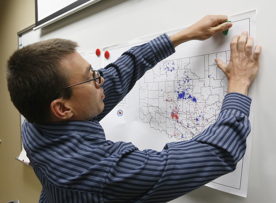 Photo - FILE - In this June 26, 2014 file photo, Austin Holland, research seismologist at the Oklahoma Geological Survey, hangs up a chart depicting earthquake activity at their offices at the University of Oklahoma in Norman, Okla. A study published Thursday, July 3, 2014 by the journal Science explains how just four wells forcing massive amounts of drilling wastewater into the ground are probably causing quakes in Oklahoma. The wells seem to have triggered more than 100 small-to-medium earthquakes in the past five years, according to a study (AP Photo/Sue Ogrocki, File)