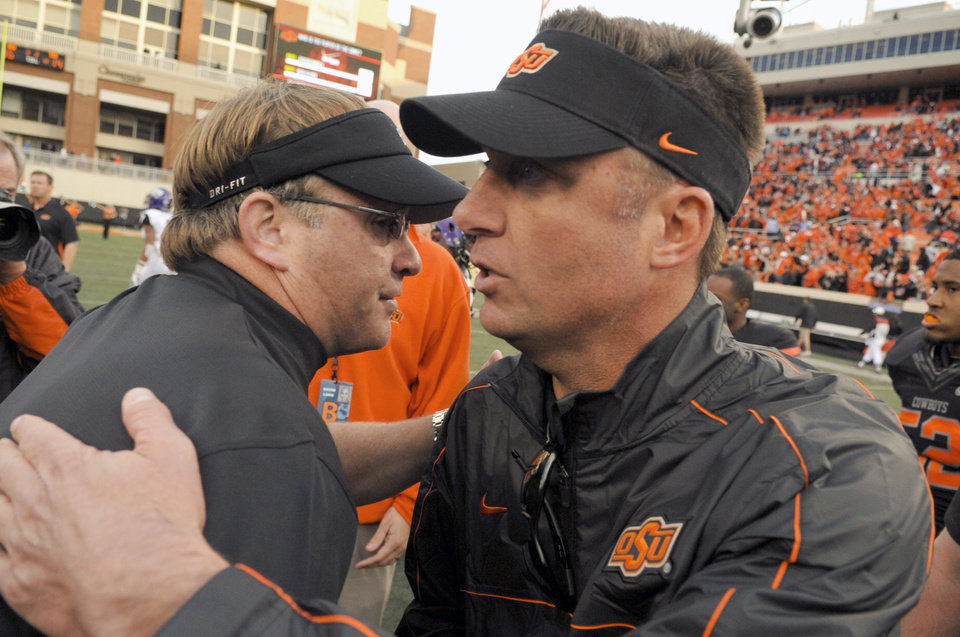 Photo -   TCU head coach Gary Patterson, left, congratulates Oklahoma State head coach Mike Gundy, right, at the end of an NCAA college football game in Stillwater, Okla., Saturday, Oct. 27, 2012. Oklahoma State won 36-14 over TCU. (AP Photo/Brody Schmidt)