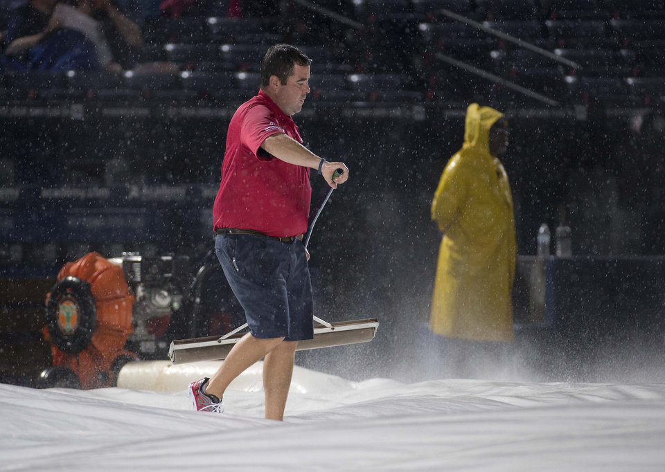 Photo - A member of the Atlanta Braves grounds crew clears water from the tarp before a baseball game between the Atlanta Braves and the Washington Nationals on Saturday, Aug. 9, 2014, in Atlanta. (AP Photo/John Bazemore)