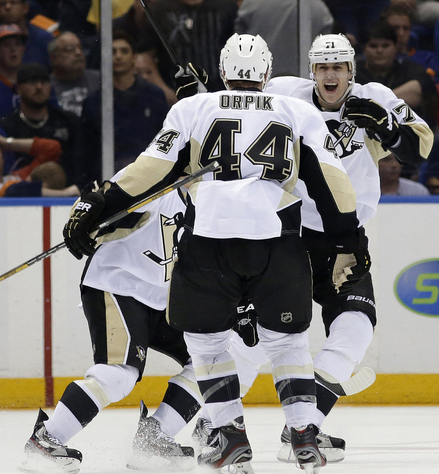 Photo - Pittsburgh Penguins center Evgeni Malkin, right, of Russia, congratulates defenseman Brooks Orpik (44), who scored the winning goal in overtime of Game 6 of a first-round NHL Stanley Cup playoff hockey series against the New York Islanders in Uniondale, N.Y., Saturday, May 11, 2013. The Penguins won 4-3. (AP Photo/Kathy Willens)