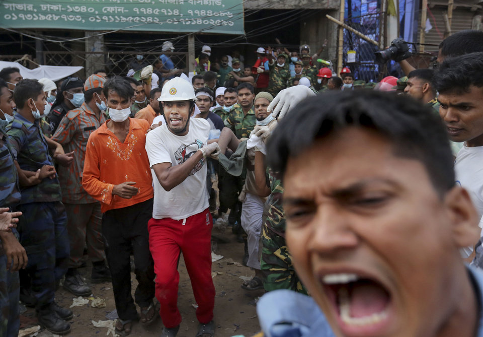 Photo - Bangladeshi rescue workers carry a garment worker who was pulled alive from the rubble at the site of a building that collapsed Wednesday in Savar, near Dhaka, Bangladesh, Friday, April 26, 2013.  Crews bored deeper Friday into the wreckage of a garment-factory building that collapsed two days earlier, hoping for miracle rescues that would prevent the death toll from rising much higher, as angry relatives of the missing clashed with police.(AP Photo/Kevin Frayer)