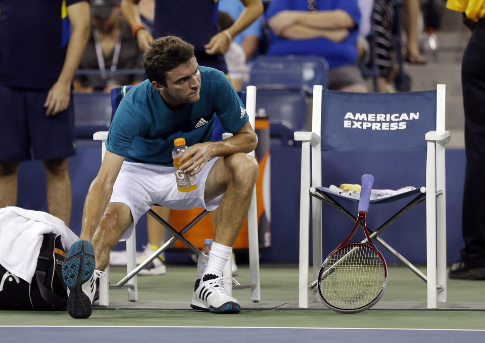 Photo -   Gilles Simon, of France, stretches between sets against Mardy Fish during a match at the U.S. Open tennis tournament Saturday, Sept. 1, 2012 in New York. (AP Photo/Darron Cummings)