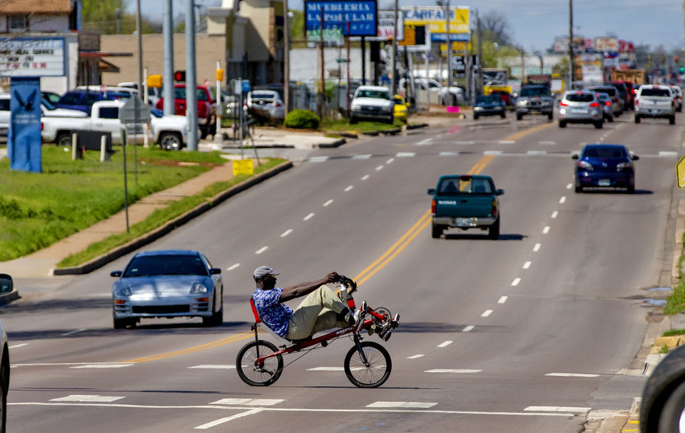 Photo - A person rides a recumbent bike down S. Blackwelder Ave. in Oklahoma City, Okla. on Tuesday, March 31, 2020. [Chris Landsberger/The Oklahoman]