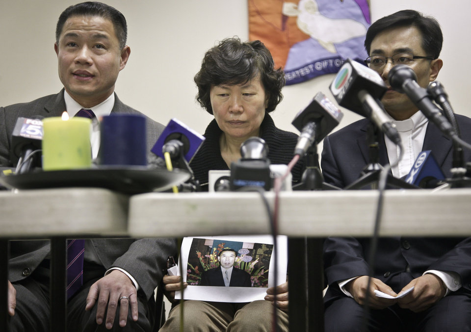 Photo - Serim Han, center, holds a picture of her husband Ki-Suck Han, as she is flanked by New York City Comptroller John Liu, left,  and Rev. Won Tae Cho, Han's pastor, during a news conference on Wednesday, Dec. 5, 2012 in New York. A homeless man was arrested Wednesday in the death of Ki-Suck Han, who was pushed onto the tracks and photographed just before a train struck him.  (AP Photo/Bebeto Matthews)