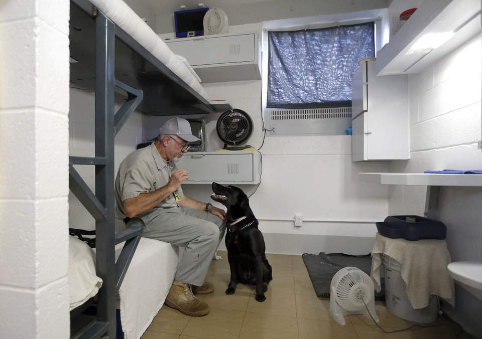 PRISON INMATES / DOGS: Inmate Steve Griffith sits in his prison cell with Dillard at the Lexington Assessment and Reception Center, Friday, July 11,  2013, in Lexington, Okla. Dillard was rescued after the May tornado.Photo by Sarah Phipps, The Oklahoman