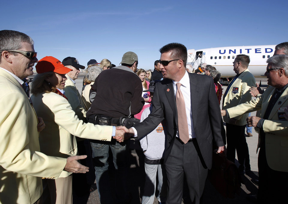 Photo - Oklahoma State coach Mike Gundy, center, is greeted by Fiesta Bowl committee members Kip Sullivan, left, and Marci Zimmerman, second from left, upon the team's arrival to play Stanford in the Fiesta Bowl NCAA college football game Jan. 2, on Monday, Dec. 26, 2011, at Sky Harbor International Airport in Phoenix. (AP Photo/Paul Connors) ORG XMIT: AZPC101