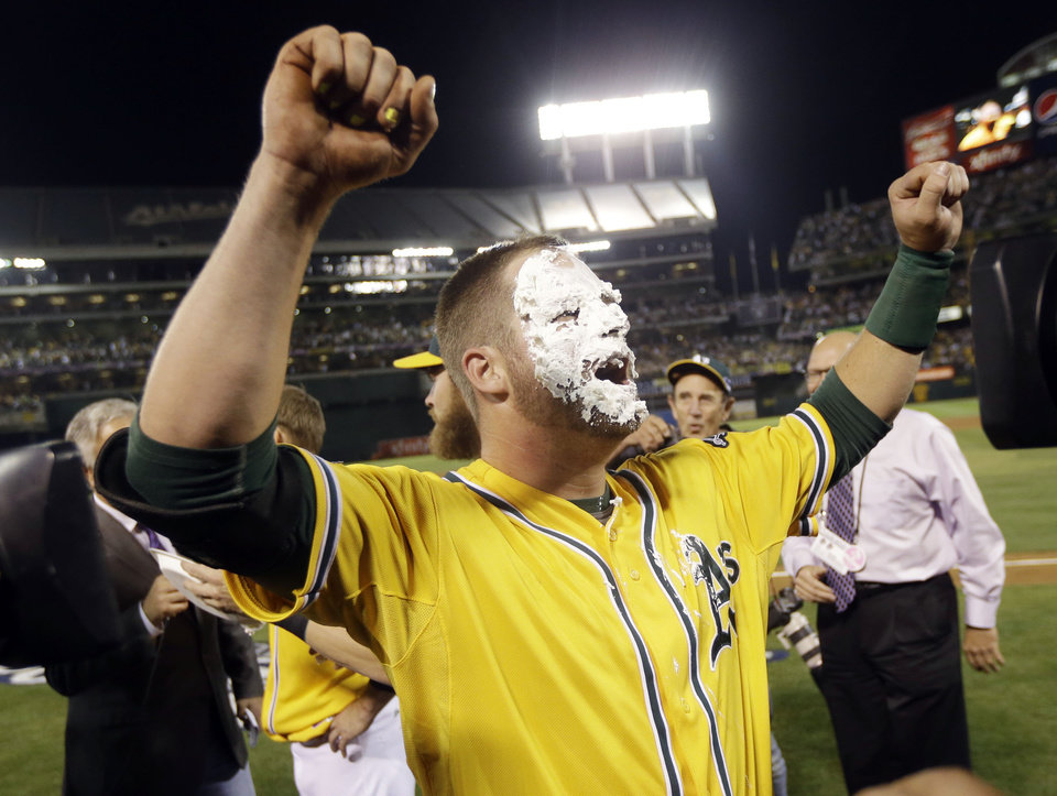 Oakland Athletics' Stephen Vogt celebrates after getting a shaving cream pie to the face from teammate Josh Reddick after Vogt made the game-winning hit to beat the Detroit Tigers 1-0 in Game 2 of the American League baseball Division Series in Oakland, Calif., Saturday, Oct. 5, 2013. (AP Photo/Marcio Jose Sanchez)