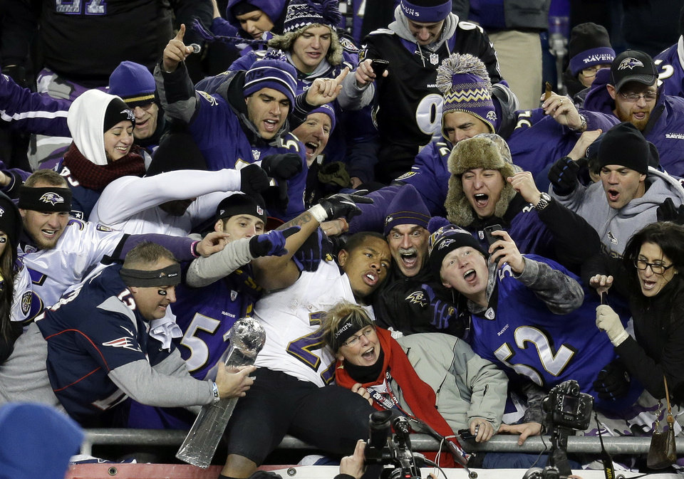 Photo - Baltimore Ravens running back Ray Rice, center, is surrounded by fans in the stands as he celebrates winning the NFL football AFC Championship football game against the New England Patriots in Foxborough, Mass., Sunday, Jan. 20, 2013. The Ravens won 28-13 to advance to Super Bowl XLVII. (AP Photo/Steven Senne)