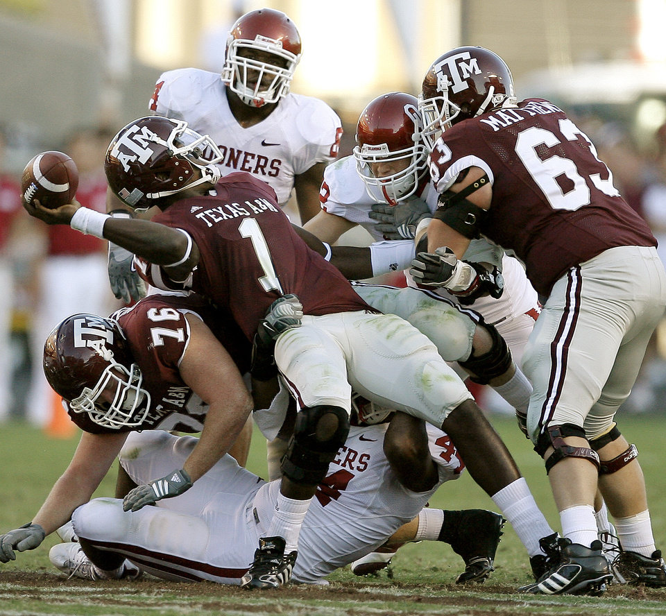Photo - Texas A&M's Jerrod Johnson tries throw the ball away as OU's Jeremy Beal tries to tackle him during the college football game between the University of Oklahoma and Texas A&M University at Kyle Field in College Station, Texas, Saturday, November 8, 2008.  BY BRYAN TERRY, THE OKLAHOMAN