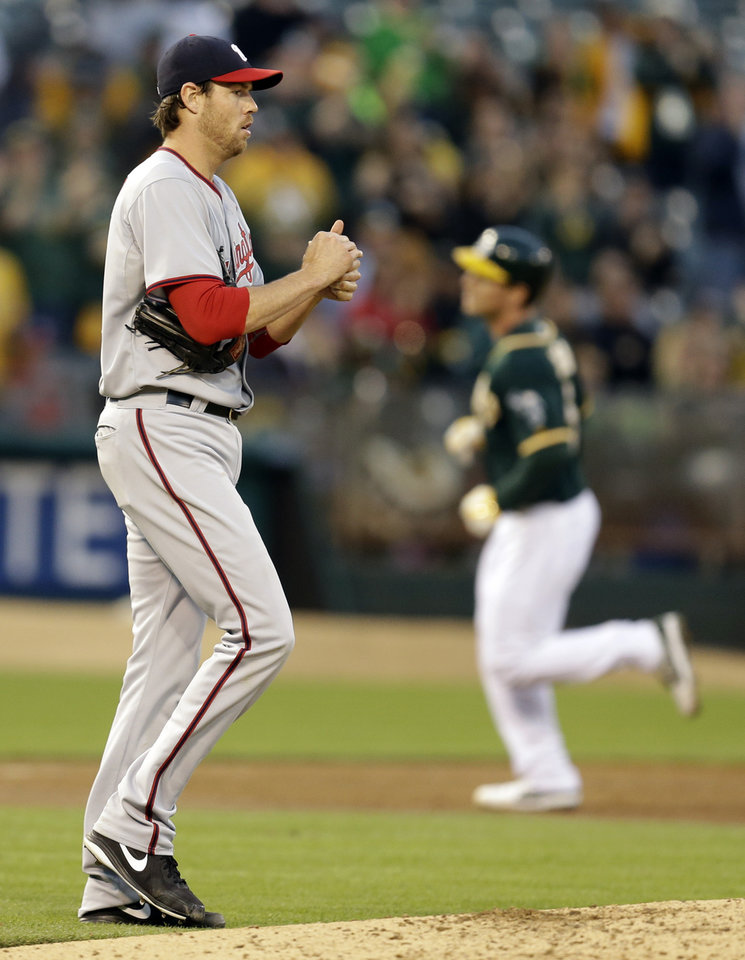 Photo - Washington Nationals' Doug Fister, left, walks back to the mound after giving up a home run to Oakland Athletics' John Jaso, right, in the third inning of a baseball game on Friday, May 9, 2014, in Oakland, Calif. (AP Photo/Ben Margot)