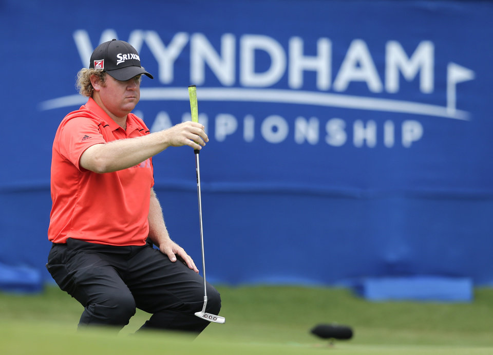 Photo - William McGirt lines up a putt on the 18th hole during the first round of the Wyndham Championship golf tournament in Greensboro, N.C., Thursday, Aug. 14, 2014. (AP Photo/Chuck Burton)
