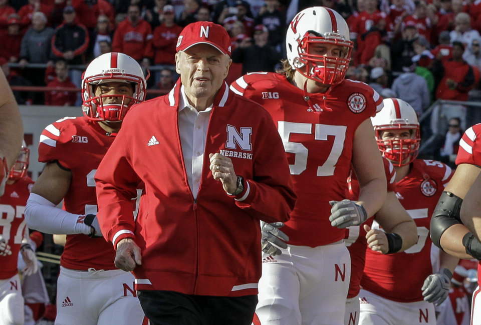 Photo - FILE - In this Nov. 17, 2012 file photo, Nebraska's retiring athletic director and former head coach Tom Osborne, center, runs onto the field with players prior to an NCAA college football game against Minnesota in Lincoln, Neb. Osborne will retire as Nebraska's athletic director on Jan. 1, 2013 and end an association with the university that began in 1962.  (AP Photo/Nati Harnik, File)