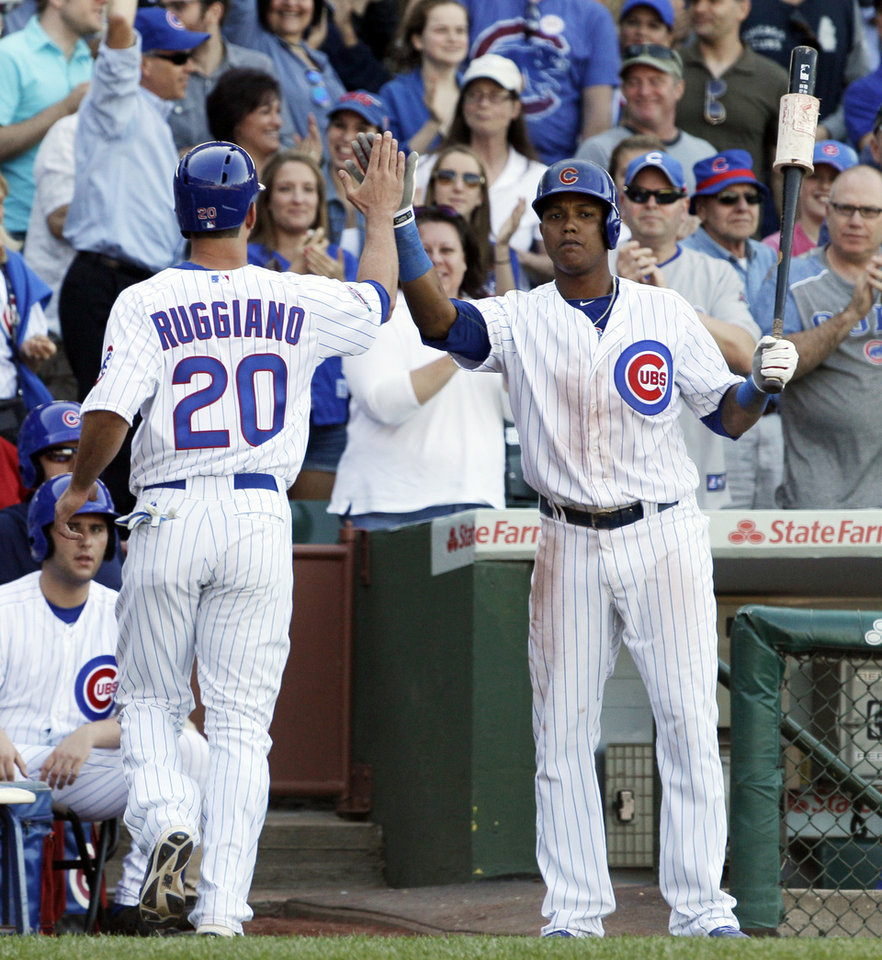 Photo - Chicago Cubs' Justin Ruggiano (20) celebrates with Starlin Castro after scoring on a two-run double hit by Anthony Rizzo during the eighth inning of a baseball game against the Miami Marlins in Chicago, Friday, June 6, 2014. (AP Photo/Nam Y. Huh)