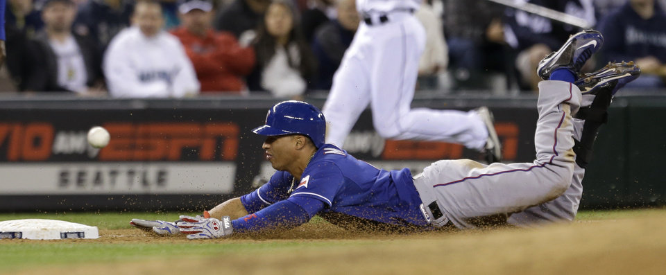 Texas Rangers' Leonys Martin slides safely toward third base on a triple against the Seattle Mariners in the sixth inning of a baseball game Saturday, May 25, 2013, in Seattle. (AP Photo/Elaine Thompson)