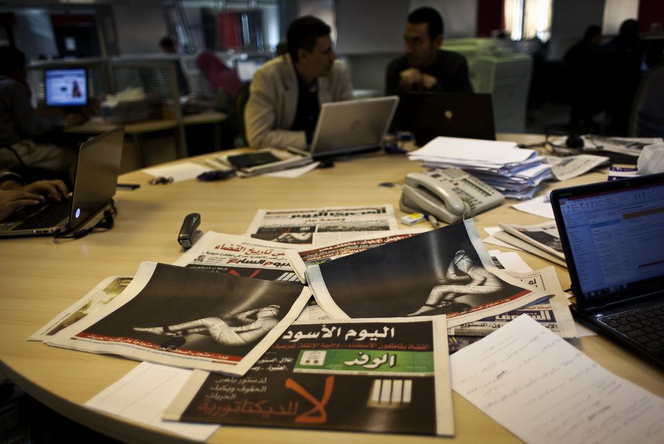 "Egyptian journalists at the editorial room of Al-Masry Al-Youm daily newspaper next to copies of Egypt's most prominent newspapers running black background front pages with Arabic that reads, ""no to dictatorship, tomorrow free newspapers will obscure to protest the freedom's restrictions,"" and a picture of a man wrapped in newspapers with his feet cuffed, in Cairo, Egypt, Monday, Dec. 3, 2012. Eleven Egyptian newspapers are planning to suspend publication on Tuesday to protest against President Mohammed Morsi's decision to call a constitution referendum on 15 December. (AP Photo/Nasser Nasser)"