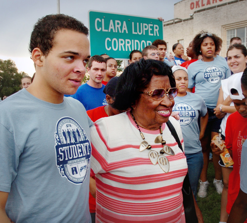 Photo - Jeff Riles escorts Clara Luper as he and other Clara Luper scholars gather near the state Capitol to remove trash from a stretch of NE 23rd street in Oklahoma City on Saturday,  August 27, 2005.  Oklahoman photo by Steve Sisney