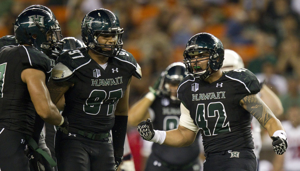 Photo - Hawaii linebacker Kamalani Alo (47) an defensive lineman Tavita Woodard (97) look on as their teammate defensive lineman Paipai Falemalu (42) celebrates sacking Southern Alabama quarterback Ross Metheny in the second quarter of an NCAA college football game Saturday, Dec. 1, 2012, in Honolulu. (AP Photo/Eugene Tanner)