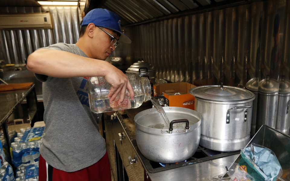 Photo - Tiep Nguyen, with Heo's, prepares food for rescue workers inside his mobile kitchen as volunteers work to aid tornado victims and rescuers on Tuesday, May 21, 2013 in Moore, Okla. Photo by Steve Sisney, The Oklahoman